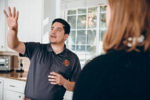 water damage restoration technician talking to customer