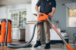 water damage restoration professional extracting water in living room