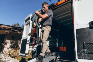 disaster restoration technician taking equipment out of van